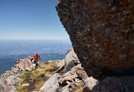 Runner athlete with beard in orange shirt running on the trail high in the mountains Stok Fotoğraf