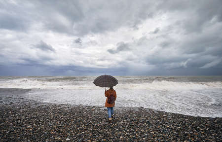 Woman with umbrella and backpack looking at stormy sea and overcast sky in Batumi, Georgia Stok Fotoğraf