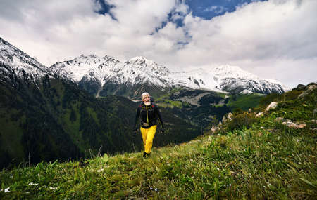 Portrait of tourist with grey beard and yellow pants in the snowy mountains. Outdoor travel concept Stok Fotoğraf