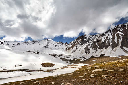 Landscape of snow mountain valley and lake against cloudy sky in Kazakhstan