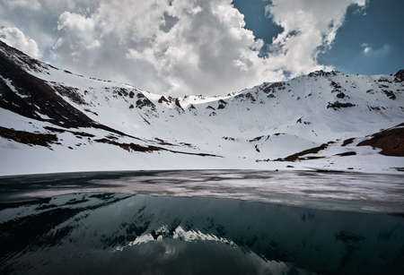 Landscape of snow mountain valley and lake with ice and reflection against cloudy sky in Kazakhstan Stok Fotoğraf
