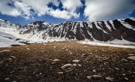 Landscape of snow mountain valley against cloudy sky in Kazakhstan Stock fotó
