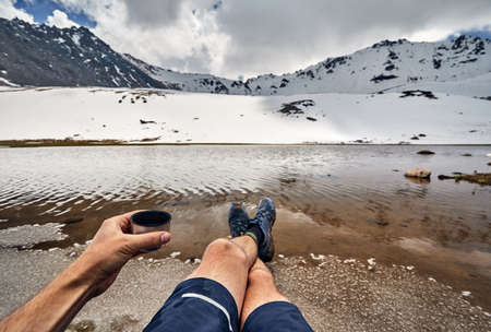 Cup of tea and legs of man in tracking shoes and view of Snowy glacier on the lake in the mountains