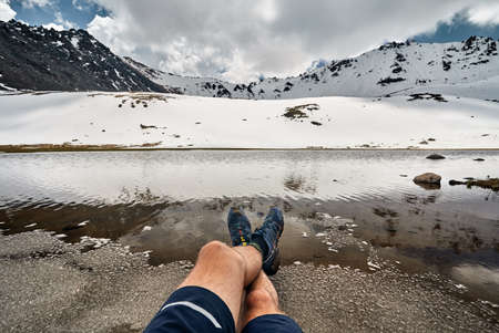 Legs of man in tracking shoes and view of Snowy glacier on the lake in the mountains