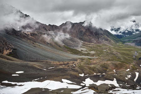 Two small climbers at glacier at mountain valley with overcast rainy clouds in Altyn Arashan gorge, Kyrgyzstan