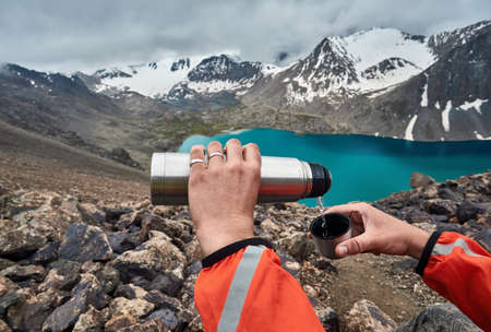 Man pouring hot tea from flask to the cup at mountain lake background. Ala-Kul lake Karakol national park, Kyrgyzstan