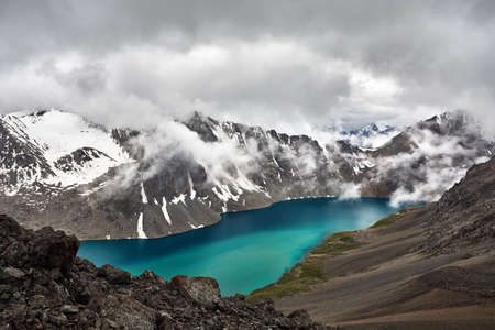Beautiful landscape of turquoise Ala-Kul Lake in the Tien Shan mountains with white foggy clouds in Karakol national park, Kyrgyzstan