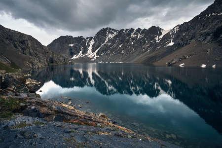 Beautiful landscape of Ala-Kul Lake with reflection of  Tien Shan mountains in Karakol national park, Kyrgyzstan