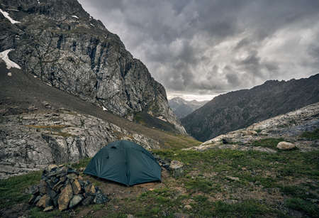Green tent in the grey mountain valley with overcast rainy clouds in Karakol national park, Kyrgyzstan