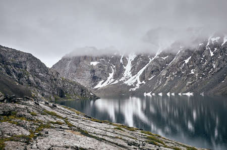 Beautiful landscape of Ala-Kul Lake in the Tien Shan mountains with white foggy clouds in Karakol national park, Kyrgyzstan