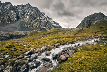 Dramatic scenery of foggy mountains and river in Altyn Arashan George, Kyrgyzstan
