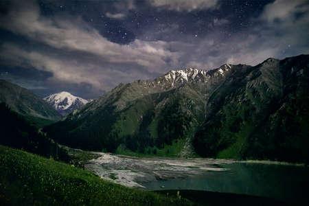 Big Almaty Mountain Lake in Tien Shan Mountains under nigh starry sky in Kazakhstan