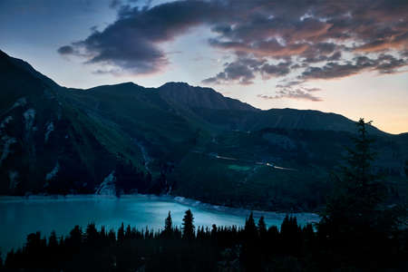 Big Almaty Mountain Lake and Big Almaty Peak at cloudy sunset sky at Tien Shan mountains, Kazakhstan