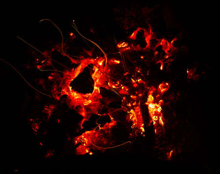 Glowing hot coals in bonfire close up background texture