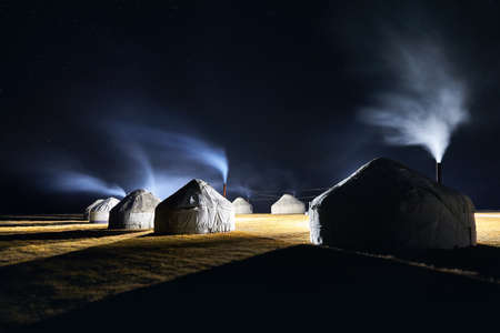 Yurt nomadic houses camp with smoke from the chimney at night sky with stars in Central Asia