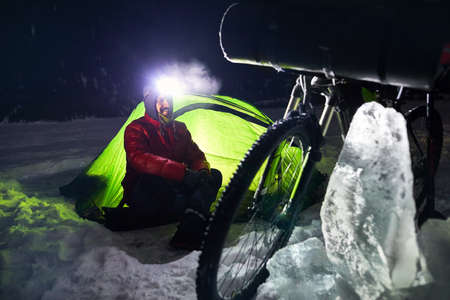 Bearded man with headlamp in the camp is sitting near bicycle and green tent at frozen lake in the mountains.