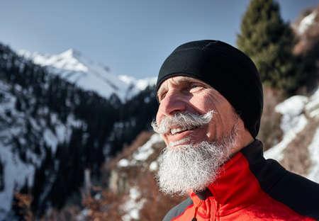 Portrait of elderly runner man with grey beard smiling against winter mountain background