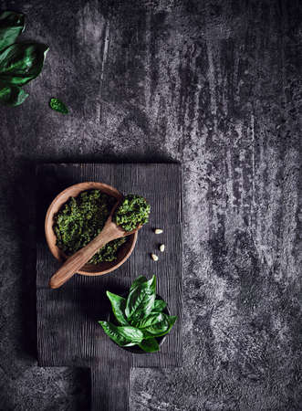 Pesto sauce from green basil, parmesan, garlic, pine nuts in wooden rustic bowl with spoon on dark grunge textured background