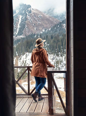 Woman in hat with at wooden house in the mountain resort at winter