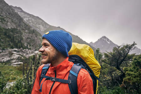 Portrait of happy tourist with big backpack is in the mountain valley of Karakol national park, Kyrgyzstan