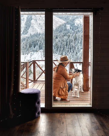 Woman in hat is playing with her dog at wooden house in the mountain resort at winter Reklamní fotografie