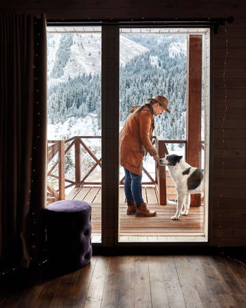 Woman in hat is playing with her dog at wooden house in the mountain resort at winter 免版税图像