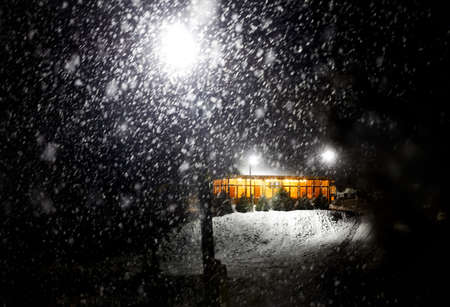 Modern wooden house with yellow glowing light it the mountain resort at snow fall storm at night