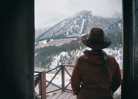 Silhouette of woman in hat at wooden house in the mountains 免版税图像