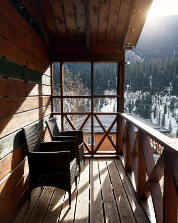 Terrace of wooden house with cozy chairs in the mountain resort at sunrise