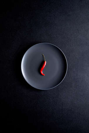 Minimalist composition of red chili pepper in black ceramic plate at black table