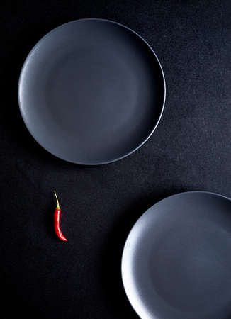 Minimalist composition of red chili pepper and two black ceramic plates at black table