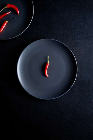 Minimalist composition of red chili peppers in to black ceramic plates at black table Reklamní fotografie