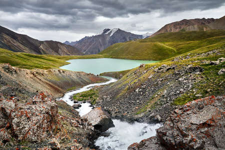 Beautiful scenery of the river and Lake Teshik Kol the mountain valley at dramatic cloudy sky in Kyrgyzstan