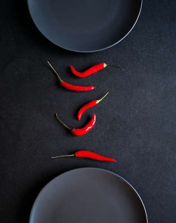 Minimalist composition of red chili peppers between two ceramic plates at black table