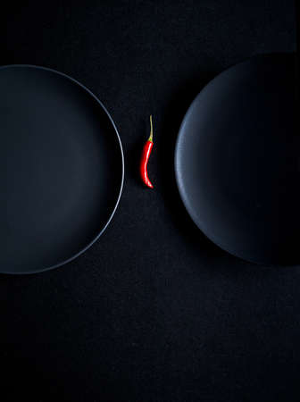Minimalist composition of red chili pepper between two ceramic plates at black background
