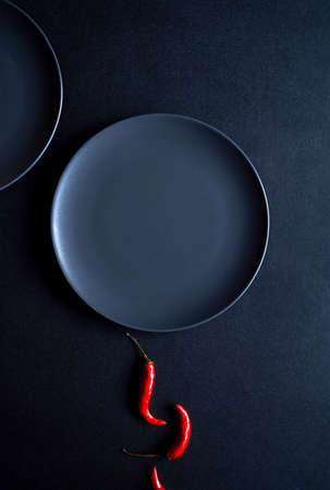 Minimalist composition of red chili peppers and two ceramic plates at black background