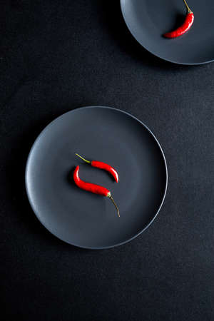 Minimalist composition of two red chili peppers in black ceramic plate at black table