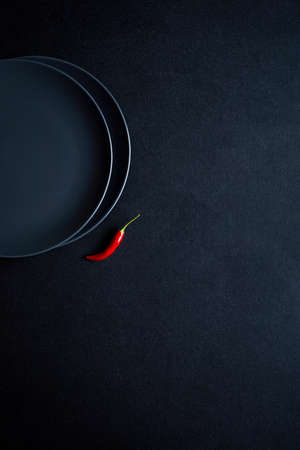 Minimalist composition of red chili pepper near two ceramic plates at black table 免版税图像