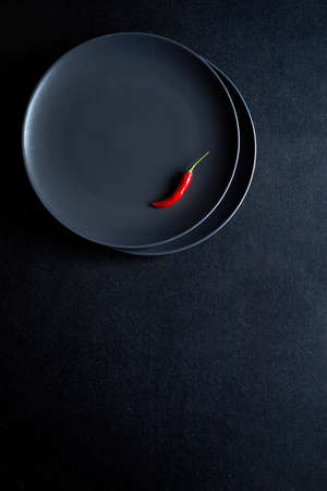 Minimalist composition of red chili pepper in the ceramic plate at black table