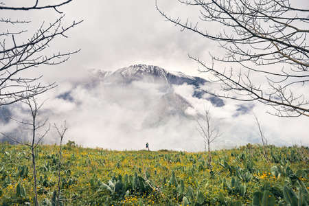 Small tourist with green backpack looking snow mountain valley in Almaty at spring time in Kazakhstan