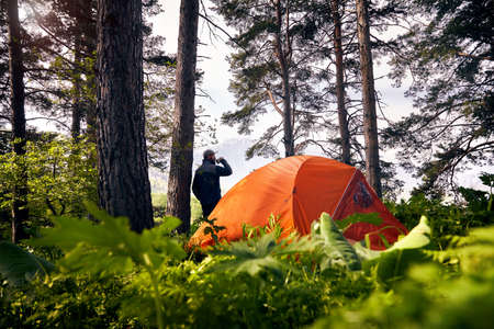 Bearded tourist is drinking coffee near orange tent in the lush forest at mountains   Stock Photo