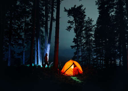 Bearded Man silhouette is walking against tree trunk in the night forest near glowing orange tent in the mountains.