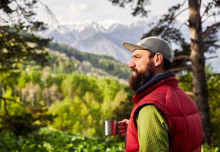 Portrait of bearded tourist is cup of coffee in the lush forest at mountains  免版税图像