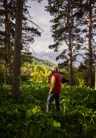 Tourist with mug of coffee in the lush forest at mountains outdoor  Reklamní fotografie