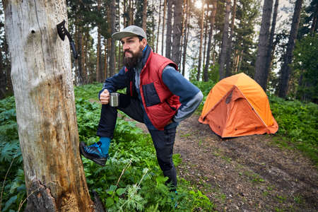 Bearded funny man with mug of coffee near orange tent at mountain forest outdoor