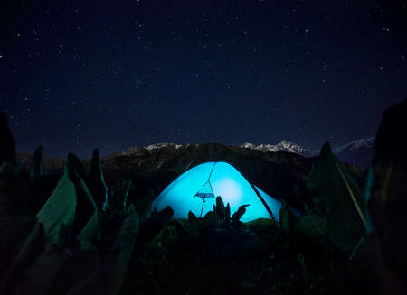 Blue gloving tent at camping in the mountain valley under night sky with stars