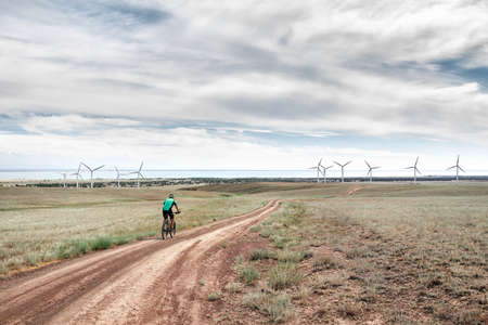 Man on mountain bike rides on the road to the wind turbines farm near the lake Against blue cloudy sky. Ecological and zero waste lifestyle concepts. 免版税图像
