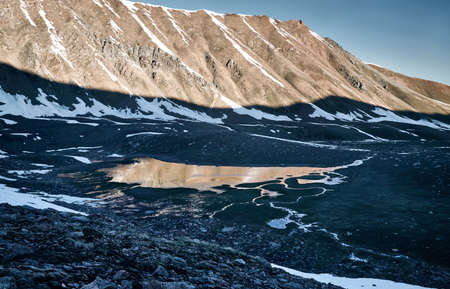 Beautiful scenery of the mountain lake with ice and reflection of snowy mountains at sunrise Reklamní fotografie