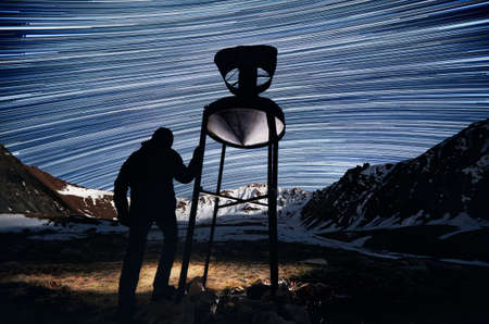 Man silhouette near old meteorological device with head light is looking at the mountains at night sky with star trails