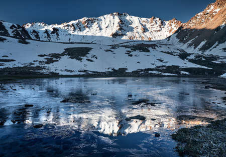 Beautiful scenery of the mountain lake with ice and reflection of snowy mountains at sunrise 免版税图像